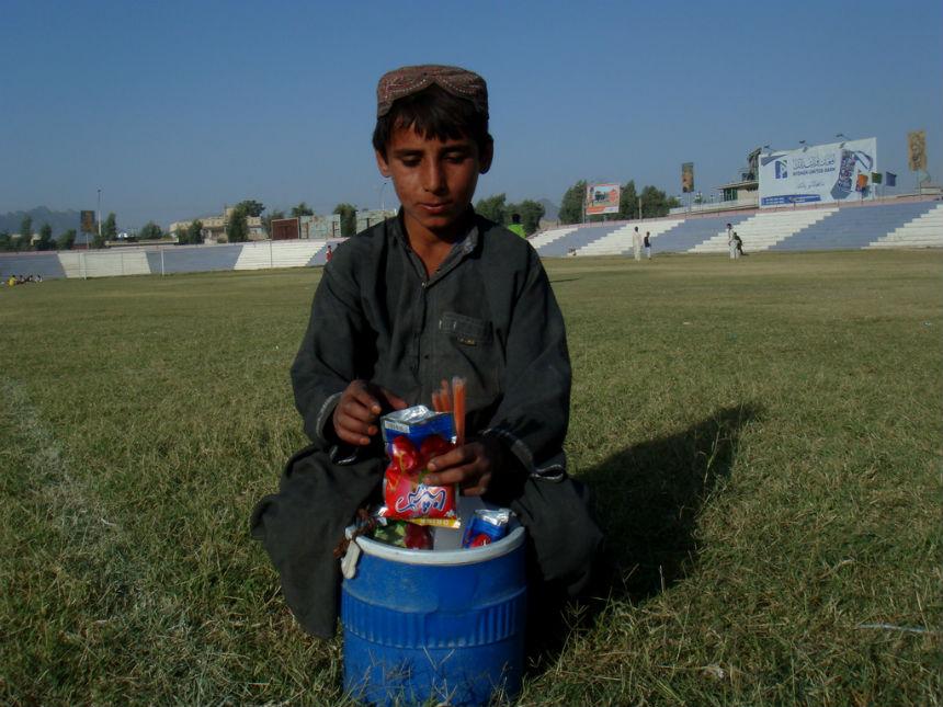 Kandahar, Afganistan. Nastolatek, po lekcjach, sprzedaje słodycze żeby zarobić dla rodziny dodatkowe pieniądze. (CC By NC ND Canada en Afghanistan)