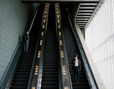 Biznesmeni w maseczkach ochronnych na schodach ruchomych w Tokio, 7 kwietnia 2020 (EPA PAP)